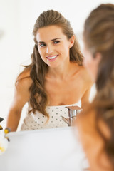 Happy young woman looking in mirror