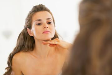 Young woman examining facial skin condition
