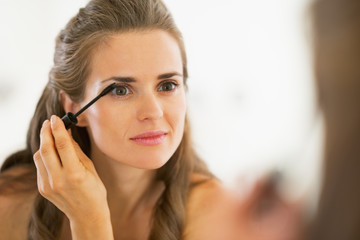 Young woman applying mascara in bathroom