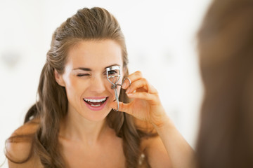 Young woman using eyelash curler in bathroom