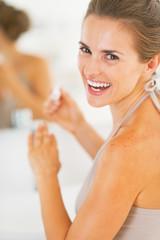 Smiling young woman applying nail polish in bathroom