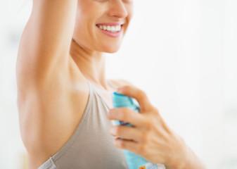 Closeup on young woman applying deodorant on underarm