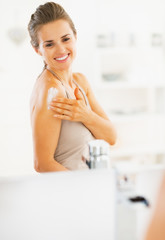 Smiling young woman applying cream in bathroom