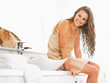 Portrait of smiling woman sitting with wet hair in bathroom