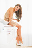 Smiling young woman sitting with wet hair in bathroom