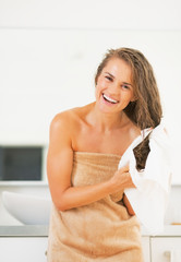 Smiling young woman wiping hair with towel