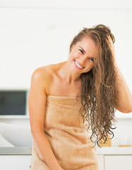 Portrait of smiling young woman wet hair in bathroom