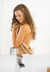 Portrait of happy young woman in towel in bathroom