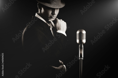 low key portrait of jazz singer in hat in the darkness.