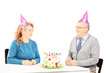Middle aged couple on table with cake, looking at each other on