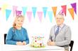 Senior couple sitting on table with big cake and celebrating bir