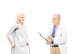 Male doctor talking to female patient on crutches