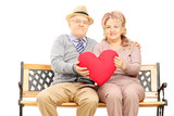 Mature couple seated on bench holding a big red heart