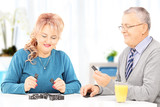 Mature couple seated on table playing dominos at home