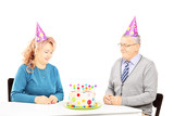 Middle aged couple sitting at birthday party looking at cake