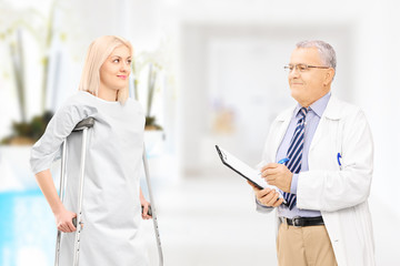 Male doctor talking to female patient with crutches in hospital