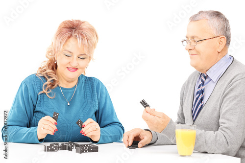 Middle aged man and woman sitting at table and playing dominos