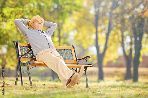 Senior gentleman sitting on a bench and relaxing in a park
