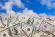 U.S. banknotes falling from the blue sky.