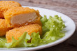 chicken nuggets and lettuce on a white plate