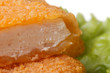 Fresh chicken nuggets cut into green lettuce close up. macro