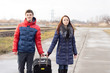 Smiling young couple pulling along a suitcase