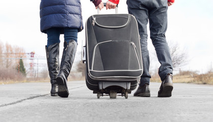 Low angle view of a couple pulling a suitcase