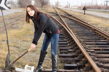 Young woman changing the points on a rail track