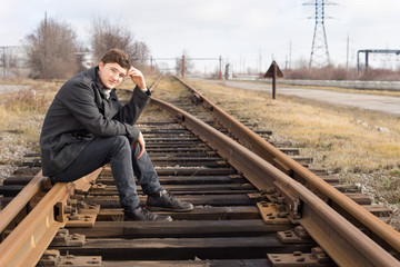 Young man sitting on the metal track of a railroad