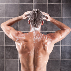 Handsome man taking a shower and enjoying it