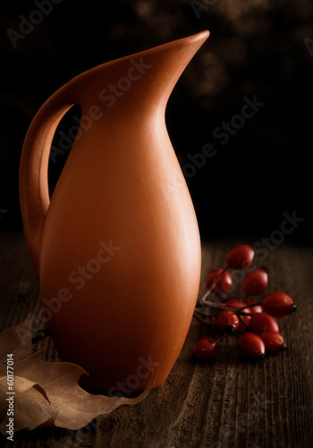 Autumn Still Life with Jug, Leaf and Rosehip. Wooden Background.