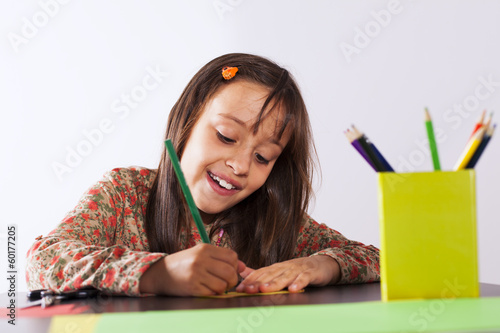 Little girl drawing with a pencil