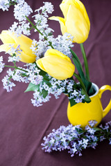 Bouquet of spring flowers on yellow vase