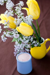 Homemade yogurt with berries and a bouquet of spring flowers