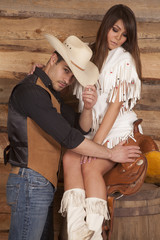 Cowboy and Indian woman sit saddle tip hat