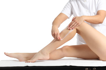 Beautician waxing a beautiful smooth woman legs with a wax strip