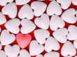 Pink heart between a pile of white hearts. Candy