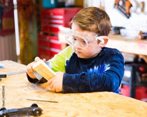 Boy sanding wooden block as he builds car for Pinewood Derby