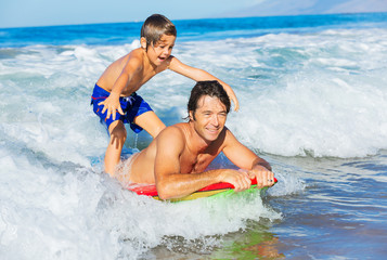 Father and Son Surfing Tandem Togehter Catching Ocean Wave, Care