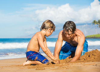 Father and son playing together in the sand on tropical beach