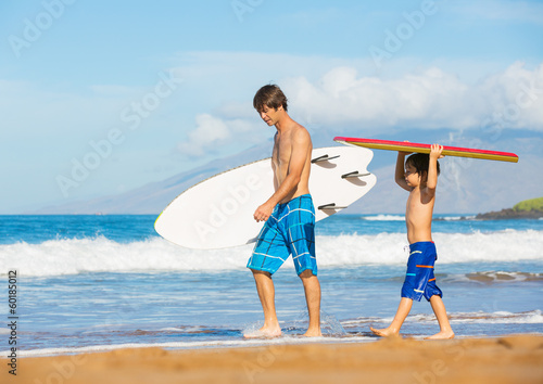 Father and Son Going Surfing Together on Tropical Beach in Hawai