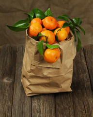 Fresh tangerines with leaves in recycle paper bag on wooden tabl