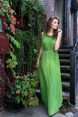 Young woman in green long dress walking outsige her home