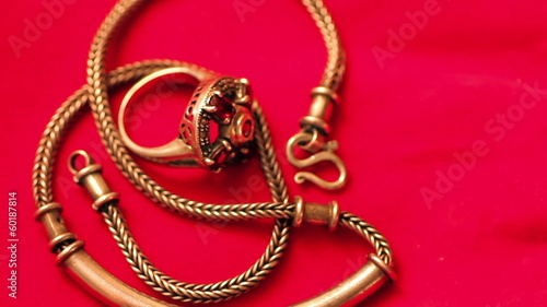 Gold chain and a ring on a red cloth