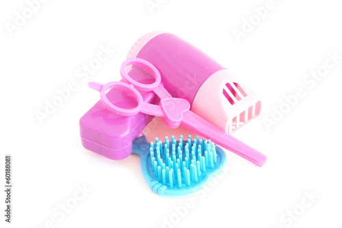 hair dryer ,scissors and comb plastic toys on white background