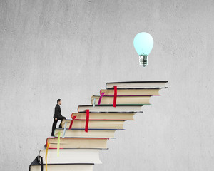 Businessman climbing on stack of books to reach top with bulb