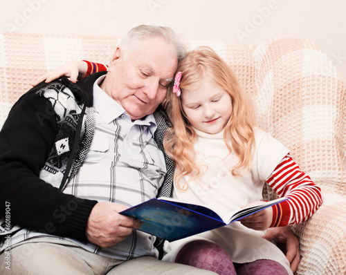 grandfather and granddaughter sitting on the sofa and reading bo