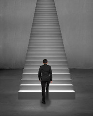 Rear view businessman climbing on stairs with spot lighting