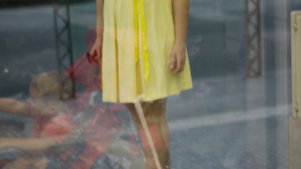 Young girl passing by a shoe shop