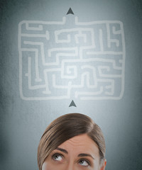 Young businesswoman looking at the labyrinth and thinking about